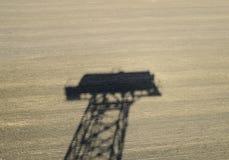 Тень водонапорной башни на вспаханном поле Стоковое Фото