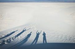 Тень группы людей на белых песчанных дюнах стоковые изображения rf