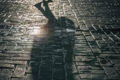 Тень женщины в пальто на старой улице в солнечном свете стоковые изображения