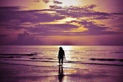 Тень женщины идя на пляж на восходе солнца стоковое изображение