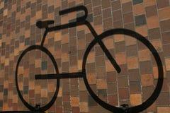 Тень от велосипеда на дороге красного кирпича в свете солнца Стоковые Изображения