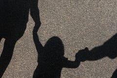Тень семьи при ребенок держа руки Стоковое Изображение