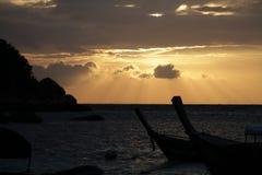 Тень шлюпки 2 и утеса перед золотыми лучами света рассвета светя через идилличные пляж и океан, предпосылки Стоковое Фото