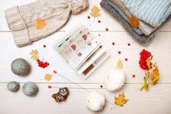 Теплые серые и голубые свитеры Связанная шляпа в белизне Путать белой и серой пряжи Вязать иглы Красная зола горы Осень выкрикива стоковые изображения rf