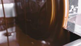 Теплый жидкостный шоколад в шоколаде закаляя машину Взгляд конца-вверх Продукция candys шоколада видеоматериал