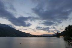 Теплый заход солнца над темным озером горы Стоковое Фото