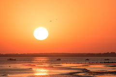 Теплый оранжевый заход солнца с огромным солнцем на береговой линии Атлантического океана Стоковая Фотография
