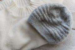 Теплый пуловер кашемира и шерстяная шляпа на белой деревянной предпосылке Стоковое Фото