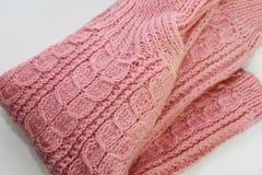 Теплый розовый связанный свитер лежит на белой предпосылке стоковая фотография