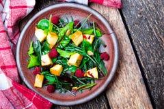 Теплый салат тыквы с полениками и смешанными лист arugula, мангольда, в коричневой плите на деревянной деревенской предпосылке Вз стоковое фото