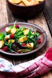 Теплый салат тыквы с полениками и смешанными лист arugula, мангольда, в коричневой плите на деревянной деревенской предпосылке ко стоковое фото