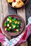 Теплый салат тыквы с полениками и смешанными лист arugula, мангольда, в коричневой плите на деревянной деревенской предпосылке Вз стоковая фотография rf