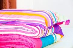 Теплая спальня с одеялом и большая пушистая подушка на кровати Стоковая Фотография
