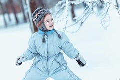 Тепло одетый мальчик играя в лесе зимы Стоковое Фото