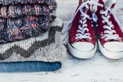 Теплые одежды и тренеры на деревянном столе Стоковая Фотография