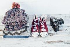 Теплые одежды, тренеры и камера фильма на деревянном столе Стоковые Фотографии RF