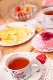 Теплые чашка чаю и помадки стоковая фотография