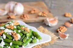 Теплый зеленый салат стручковых фасолей Зеленый салат стручковых фасолей с творогом, сырцовыми грецкими орехами, чесноком и специ Стоковое Изображение RF