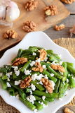 Теплый салат зеленых фасолей Простой салат зеленых фасолей с творогом, сырцовыми грецкими орехами, чесноком и специями на плите Стоковые Изображения RF