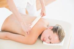Терапевт вощия заднюю часть женщины на спа-центре стоковое изображение rf
