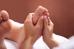 Терапевт давая массаж ноги для того чтобы укомплектовать личным составом стоковые фото