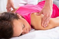 Терапевт давая массаж плеча женскому пациенту стоковое изображение rf