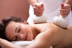 Терапевт давая массаж с травяными шариками обжатия женщине стоковая фотография rf