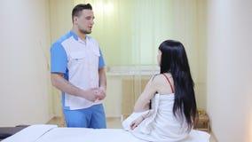 Терапевт массажа разговаривая с пациентом сток-видео