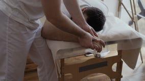 Терапевт массажирует руку молодого человека акции видеоматериалы