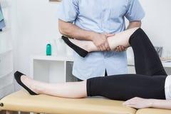 Терапевт массажируя ногу женщины Стоковая Фотография