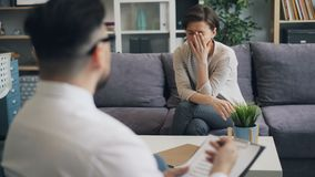 Терапевт молодого человека говоря с усиленной женщиной спрашивая вопрос работая в офисе видеоматериал