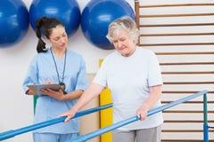 Терапевт смотря старшую женщину идя с параллельными брусьями Стоковые Фото
