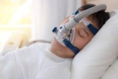 Терапия апноэ сна, человек спать в кровати нося маску CPAP Стоковое фото RF