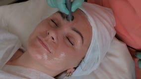 терапия Не-впрыски Cosmetologist в голубых перчатках работает с электродом на стороне красивой девушки Косметология оборудования сток-видео