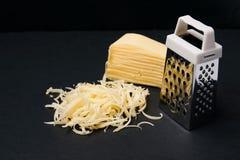 Терка и сыр на темной предпосылке шифера Стоковые Изображения