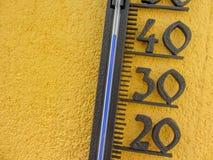 Термометр в желтой стене измеряя внешнюю температуру воздушной среды над 40 градусами Градуса цельсия Стоковые Изображения RF