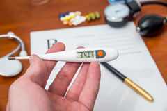 термометр в руках доктора на форме RX предпосылки Стоковые Изображения