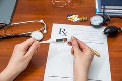 термометр в руках доктора на форме RX предпосылки Стоковое фото RF