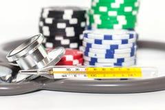Термометр и куча казино откалывают на белизне Стоковые Изображения RF