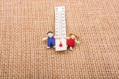 Термометр между мальчиком и figurine девушки Стоковые Фото