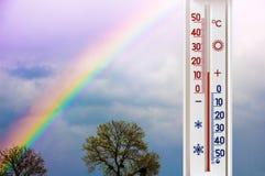 Термометр на предпосылке неба с радугой показывает 15 градусов heat_ стоковое фото