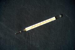 Термометр на черной предпосылке стоковая фотография rf