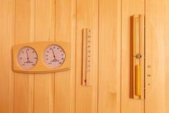 Термометр сауны и влагомер, часы на деревянной стене воцарения стоковое фото rf