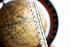 Термометр с античной предпосылкой глобуса Стоковое фото RF