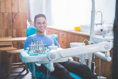 Терпеливый дантист сидя в зубоврачебном стуле стоковые изображения