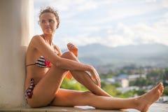 Терраса бассейна захода солнца молодой сексуальной девушки фото расслабляющая с красивым видом Усмехаясь время холодка траты женщ Стоковая Фотография