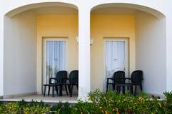Терраса белого каменного загородного дома с стеклянными дверями с пластичными стульями для остатков в задворк стоковые изображения