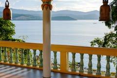 Терраса с столбцами, буддийскими колоколами, взглядом моря и горами в расстоянии Стоковые Изображения