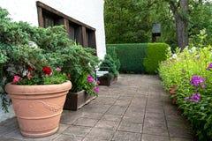 Территория дома украшена с огромным керамическим баком с цветками и хвойными деревьями стоковые изображения rf