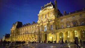 Территория Лувра толпилась много туристов осматривая дворец и пирамиды стоковая фотография
